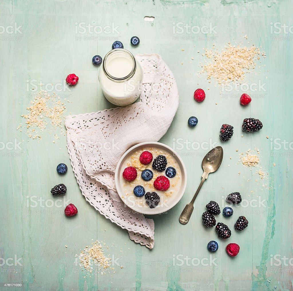 oatmeal porridge, bottle of milk and berries stock photo