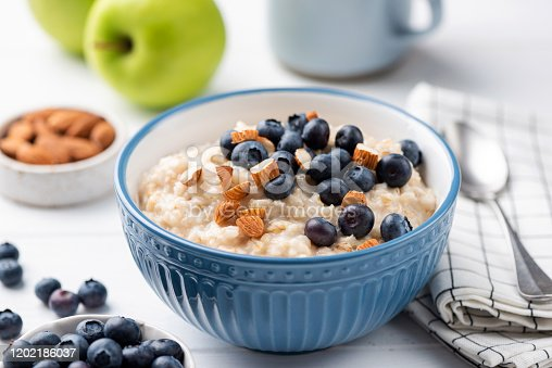 Oatmeal porridge bowl with blueberries and almonds in blue bowl. Healthy breakfast food, vegetarian breakfast high in fiber and slow carbs