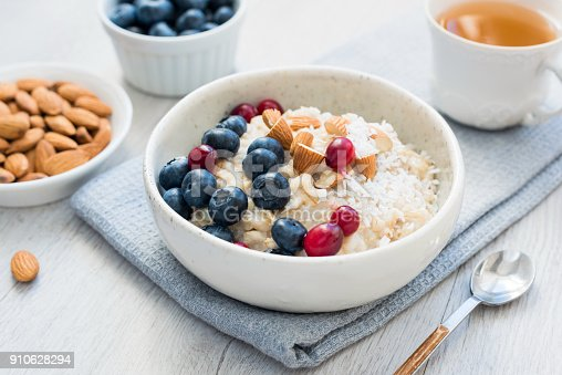 801463056istockphoto Oatmeal porridge bowl with blueberries, cranberries and almonds 910628294
