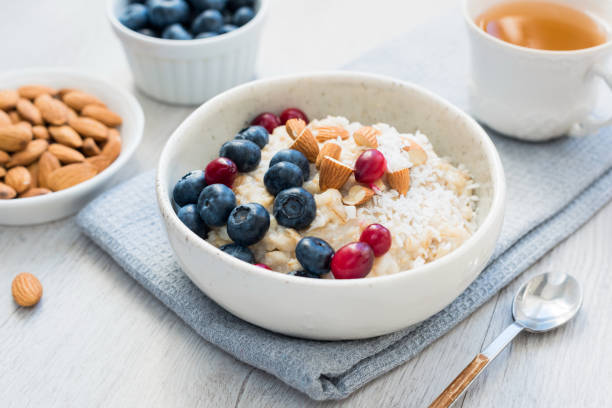 Oatmeal porridge bowl with blueberries, cranberries and almonds Oatmeal porridge bowl with blueberries, cranberries and almonds and cup of green tea. Concept of healthy lifestyle, healthy eating, fitness menu and dieting oatmeal stock pictures, royalty-free photos & images