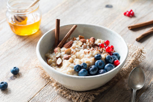 Oatmeal porridge bowl with fruits, nuts and cinnamon in bowl Oatmeal porridge with blueberries, almonds, cinnamon, honey, linseeds and red currants in bowl. Super food for healthy nutritious breakfast oatmeal stock pictures, royalty-free photos & images