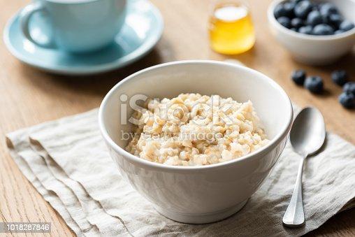 Oatmeal porridge, scottish oats in a bowl on table, kitchen linen. Healthy breakfast, healthy lifestyle concept
