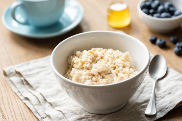 Oatmeal porridge, scottish oats in a bowl Oatmeal porridge, scottish oats in a bowl on table, kitchen linen. Healthy breakfast, healthy lifestyle concept oatmeal stock pictures, royalty-free photos & images