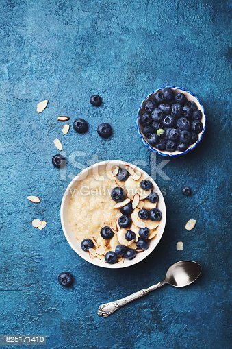 825171518 istock photo Oatmeal porridge with banana and blueberry on vintage table top view in flat lay style. Hot breakfast and diet food. 825171410