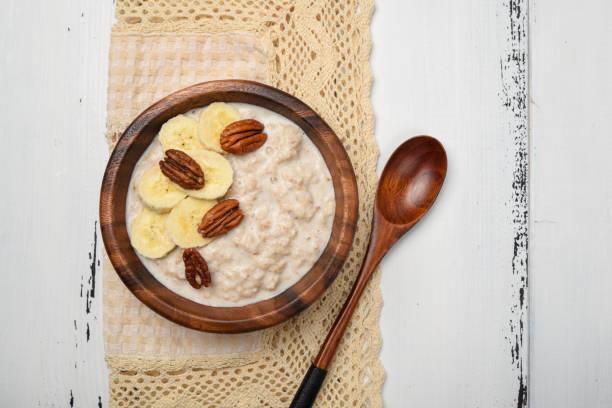 haferflocken-porridge mit banane und pecan-nüssen zum frühstück auf weißer holztisch - zimt pekannüsse stock-fotos und bilder