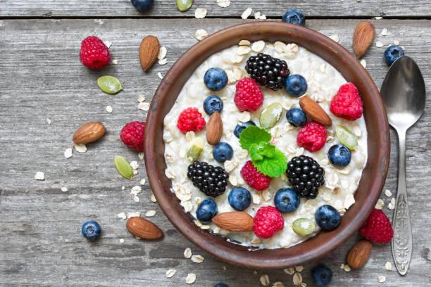 haferflocken-porridge mit beeren und nüssen in einer schüssel mit einem löffel für gesundes frühstück auf rustikalen hölzernen hintergrund - getreidebrei stock-fotos und bilder