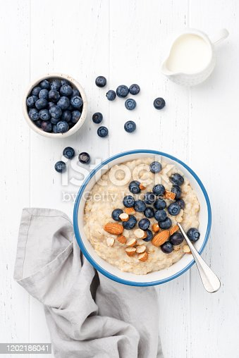 Oatmeal porridge with blueberries and almond nuts, table top view. Healthy breakfast food