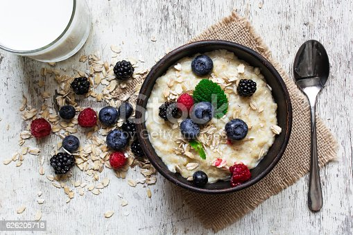 825171518 istock photo oatmeal porridge with fresh berries, glass of milk and spoon 626205718