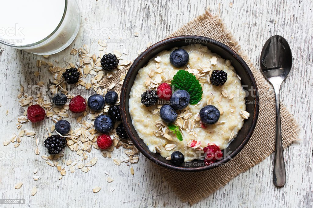 oatmeal porridge with fresh berries, glass of milk and spoon stock photo