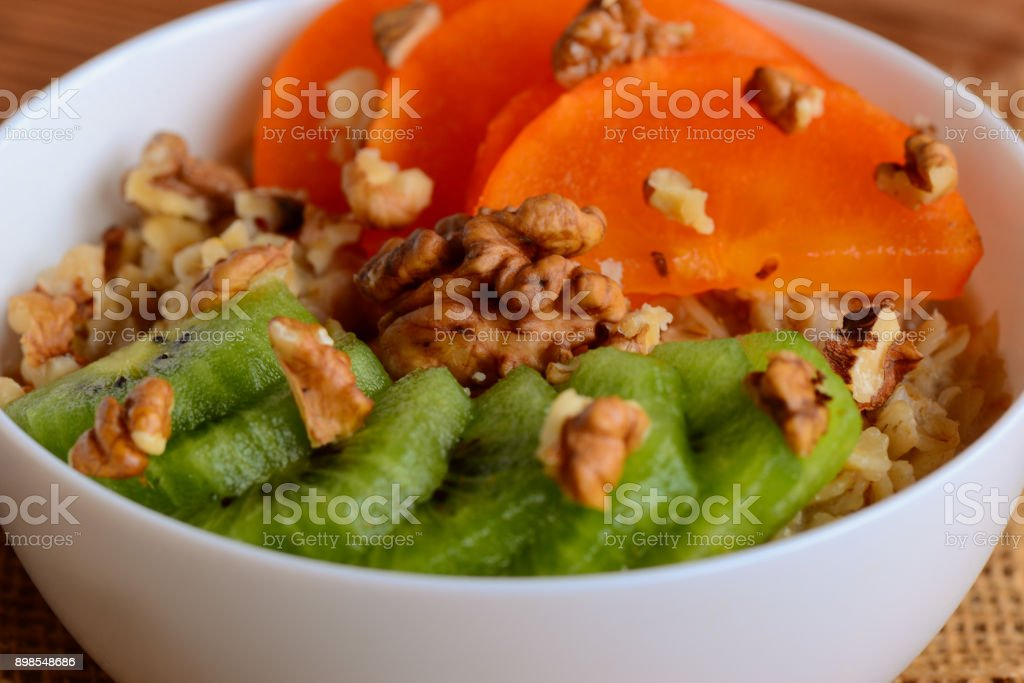 Oatmeal porridge with fresh fruits and nuts toppings. Oatmeal with fresh persimmon slices, kiwi fruit and peeled walnuts in a round white bowl. Wholesome porridge. Closeup stock photo