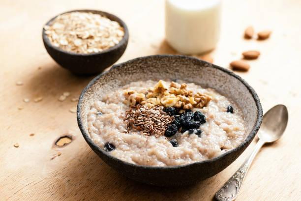 haferflocken-porridge mit rosinen und samen - haferflocken rosinen stock-fotos und bilder