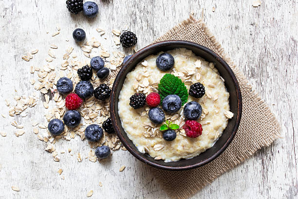 oatmeal porridge with ripe berries oatmeal porridge with ripe berries - blueberry, raspberry and blackberry for healthy breakfast. flat lay. top view oatmeal stock pictures, royalty-free photos & images