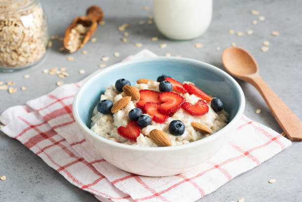 Oatmeal porridge with strawberries, blueberries and almonds Oatmeal porridge with strawberries, blueberries and almonds in a bowl. Healthy breakfast food, healthy lifestyle concept oatmeal stock pictures, royalty-free photos & images