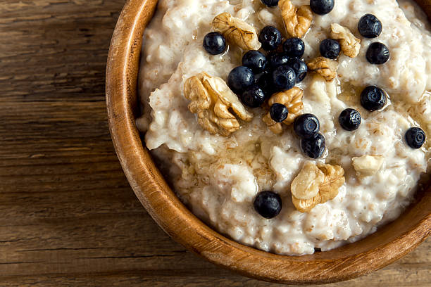 oatmeal porridge with walnuts, blueberries - oatmeal photos et images de collection