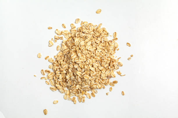 Oatmeal raw grains isolated on white background, top view. stock photo
