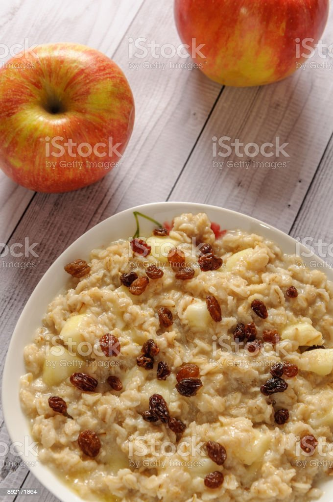 Oatmeal with apple and raisins against the background of the old tree. Muesli with an apple and raisins stock photo