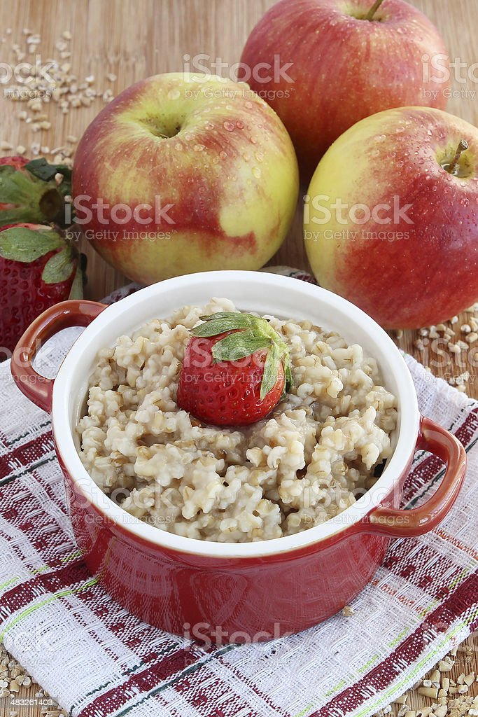 Oatmeal with apples and strawberries stock photo