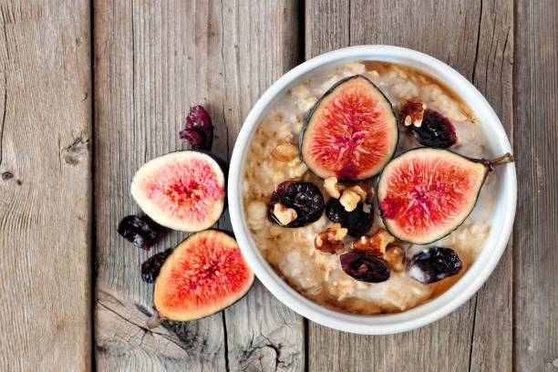 Oatmeal with figs, cranberries and walnuts over rustic wood stock photo