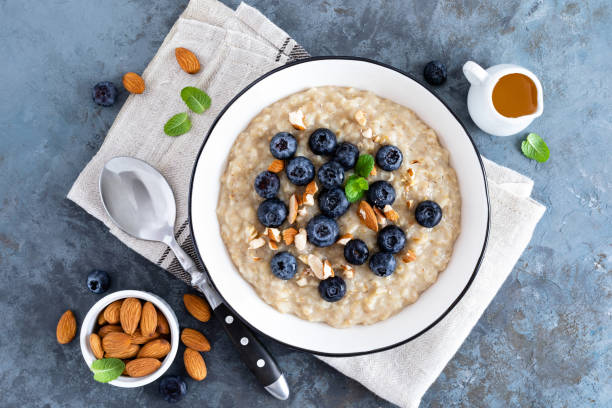 oatmeal with fresh raw blueberry, almond nuts and honey for breakfast. healthy vegetarian food. top view - porridge foto e immagini stock