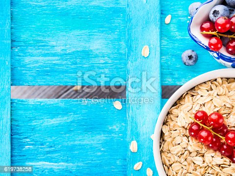 825171518 istock photo Oats and berries on light blue textured background. Copy space 619738258