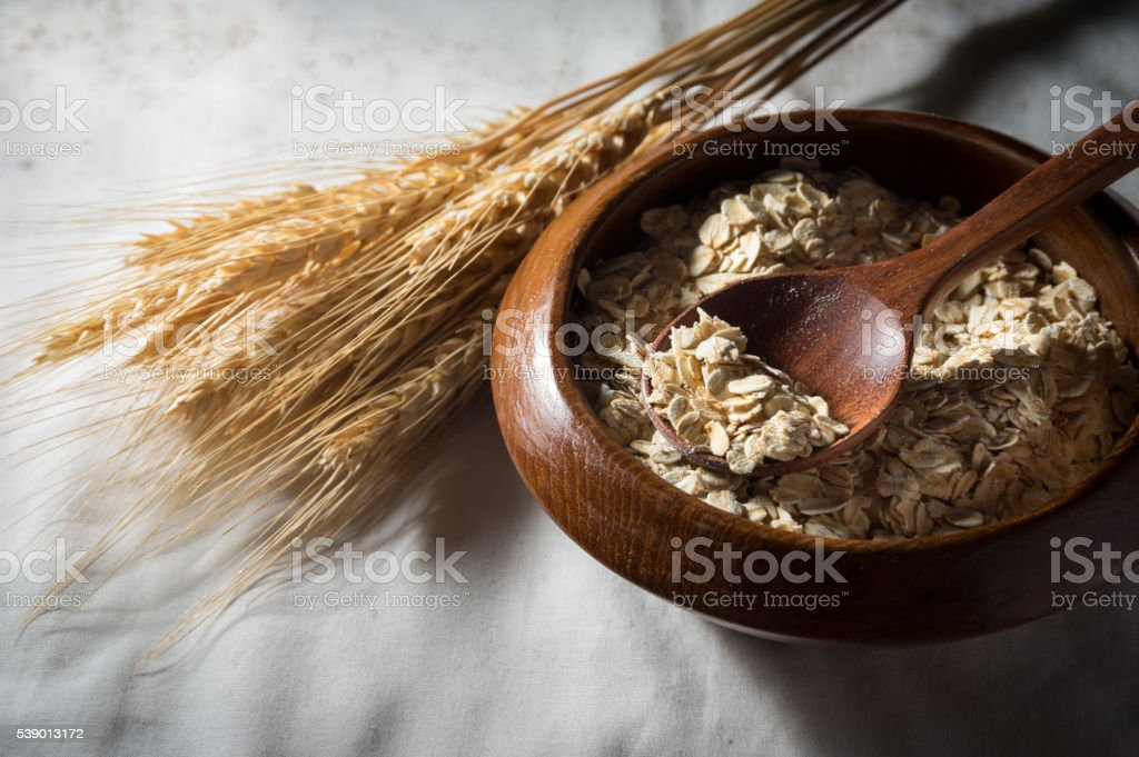 Oats and wheat in wooden bowl with spoon stock photo
