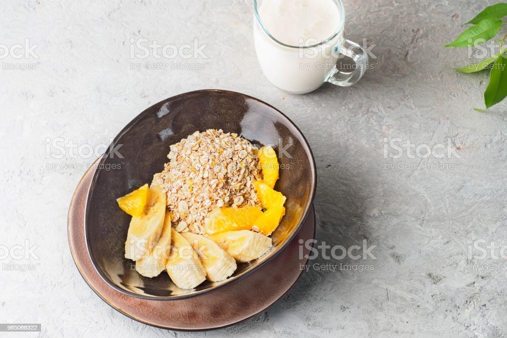 Oats Barley Wheat Rye Corn mix flake proper nutrition diet with pieces banana orange and glass of milk zbiór zdjęć royalty-free