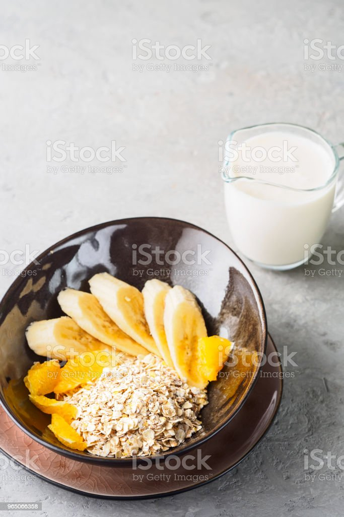 Oats Barley Wheat Rye Corn mix flake proper nutrition diet with pieces banana orange and glass of milk zbiór zdjęć royalty-free
