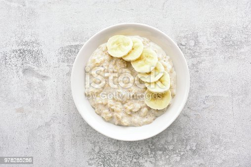 Oats porridge with banana slices in bowl over stone background. Diet healthy nutrition food concept. Top view, flat lay