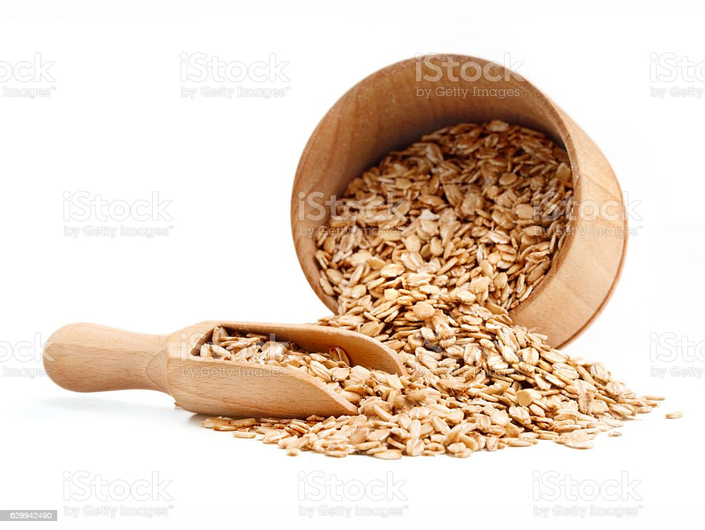 Oats scattered from wooden bowl stock photo