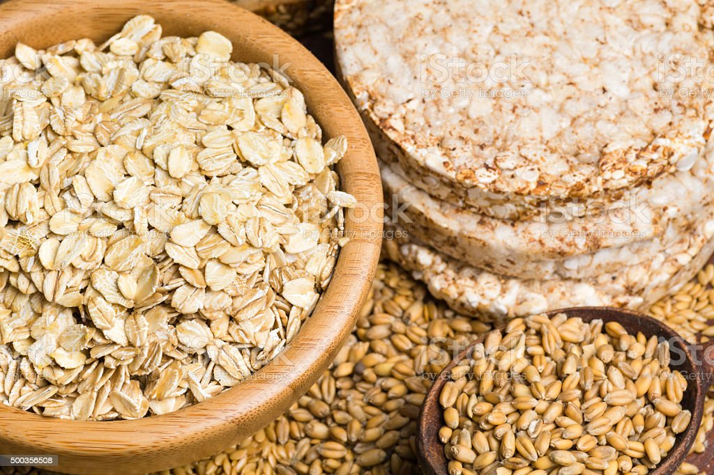 Oats, whole wheat grains, seeds and rice cakes stock photo