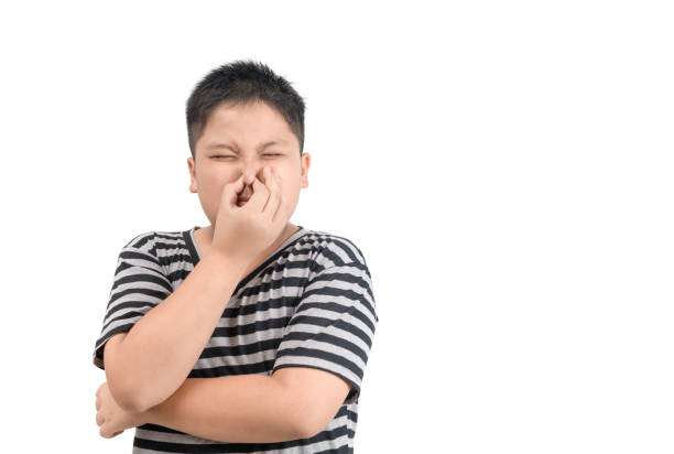 Obese boy holding his nose because of a bad smell stock photo