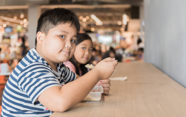Obese brother and sister eating box lunch in food court stock photo