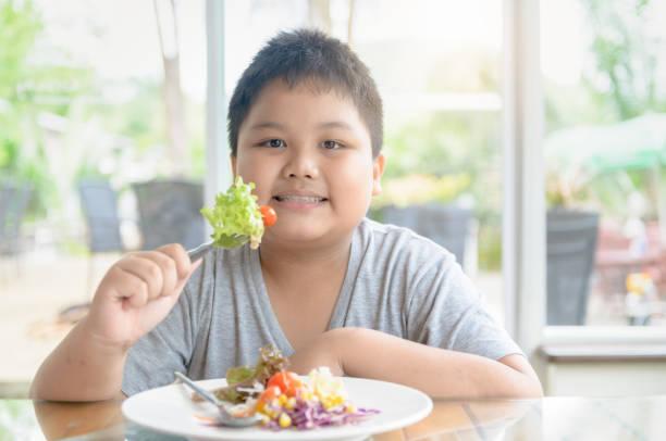 Obese fat boy enjoy to eat vegatables salad. stock photo