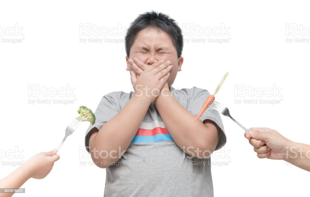 obese fat boy with expression of disgust against vegetables stock photo