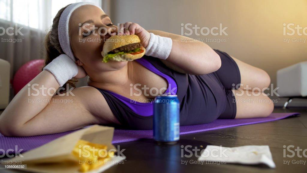 スポーツ トレーニング、モチベーションの欠如ではなく脂のハンバーガーを食べて肥満女性 - 怠惰のロイヤリティフリーストックフォト