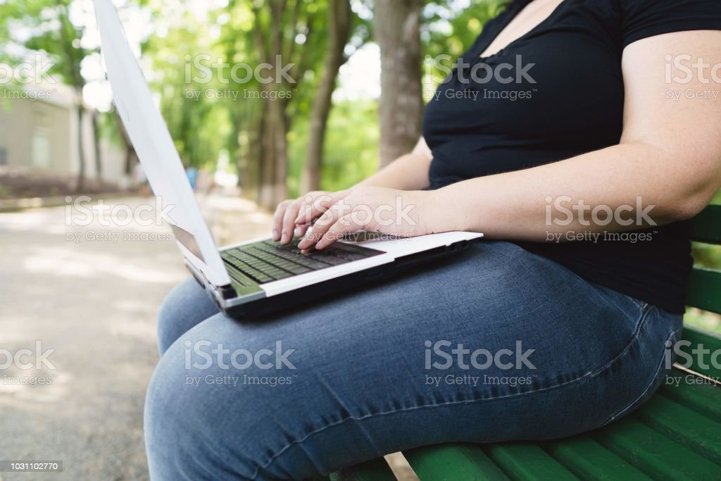 obese female worker with laptop working outdoors stock photo