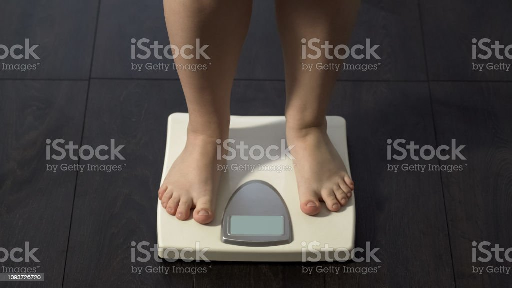 Obese girl standing on electronic scales, weight loss program,...