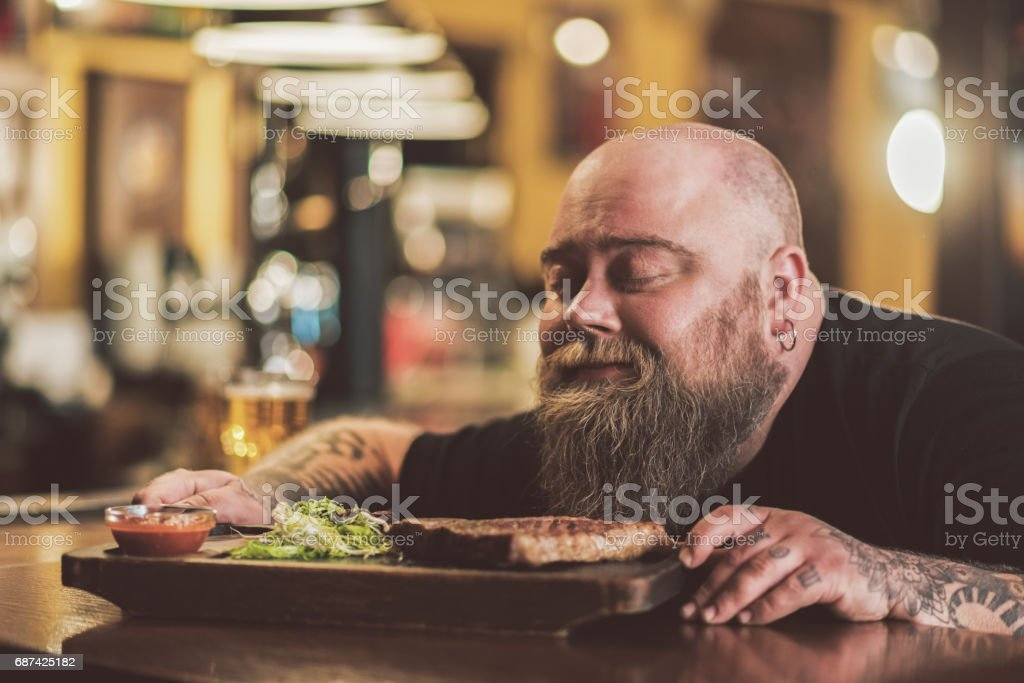 Obese male savoring grilled meat in pub stock photo