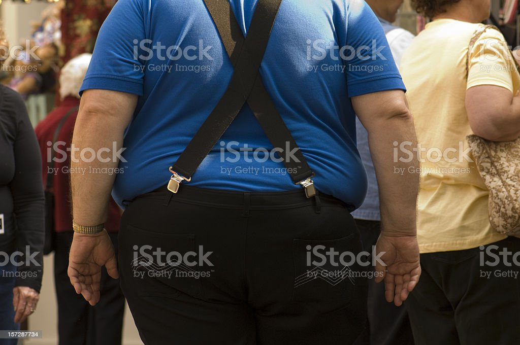 Obese Male with Blue Shirt Black Pants Suspenders Backside stock photo
