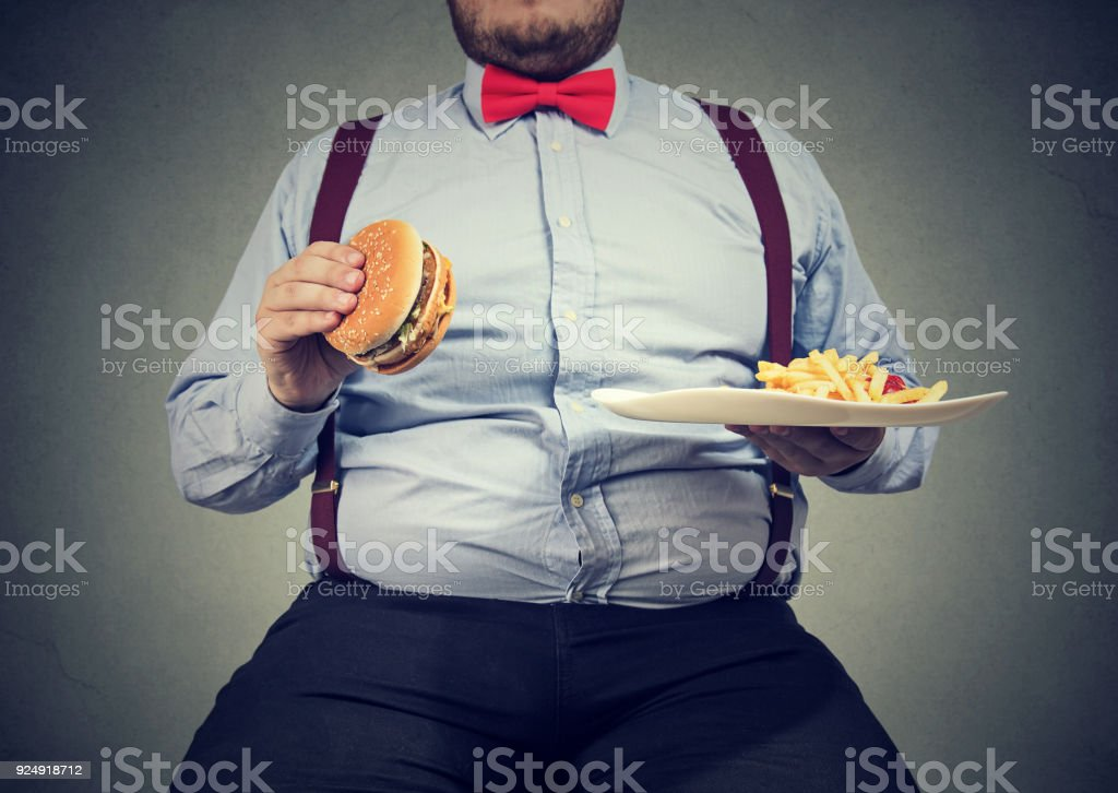 Crop shot of big man in formal clothes sitting and consuming plate...