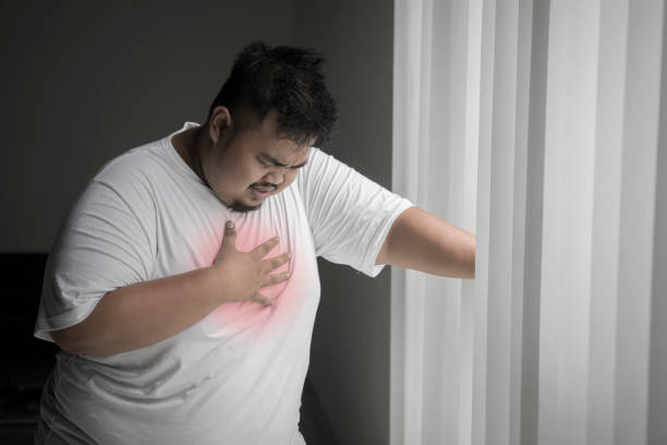 Obese man having a heart attack near the window stock photo