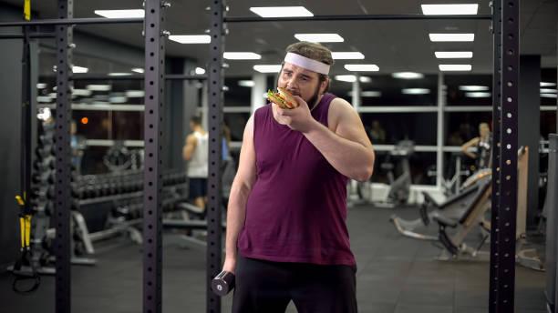 übergewichtigen mann, hält hantel essen burger, ablehnung zu tun, sport, sucht - gewicht schnell verlieren stock-fotos und bilder