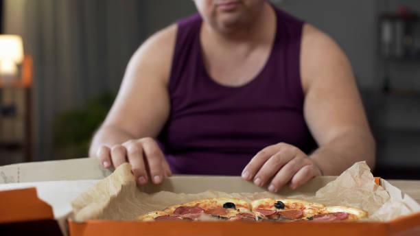 zwaarlijvige man kijken naar vette pizza op tafel, junkfood verslaving, overeten - dikke pizza close up stockfoto's en -beelden