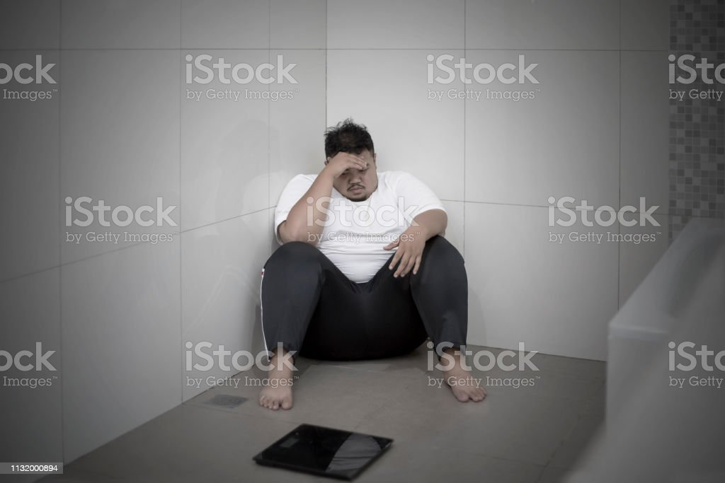 Obese man looks unhappy while sitting with a scale in the bathroom....