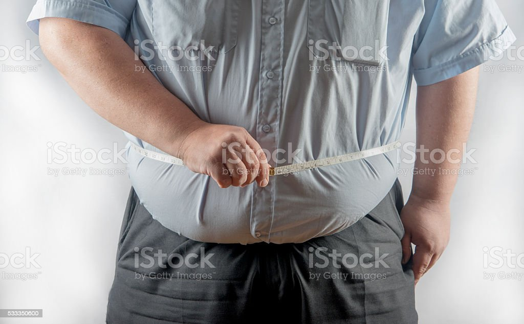 Obese man measuring his waist stock photo