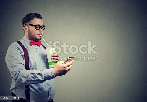 1067846662 istock photo Obese man with soda and phone 969119524