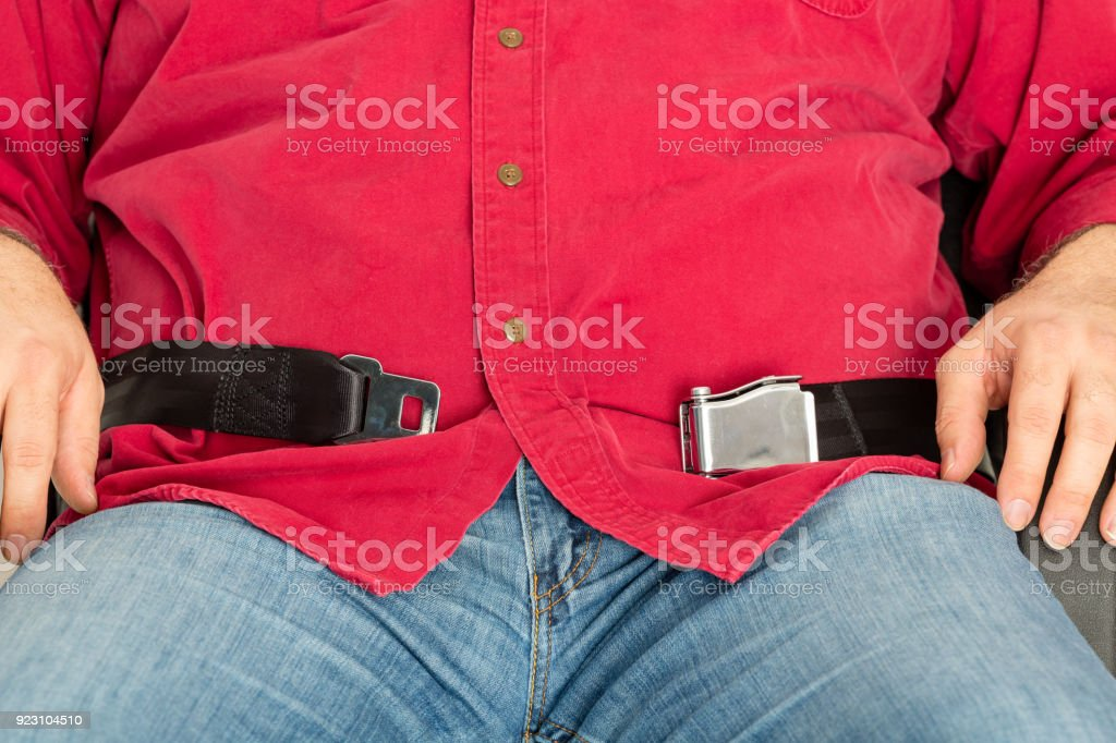 Obese passenger unable to fasten the seatbelt stock photo