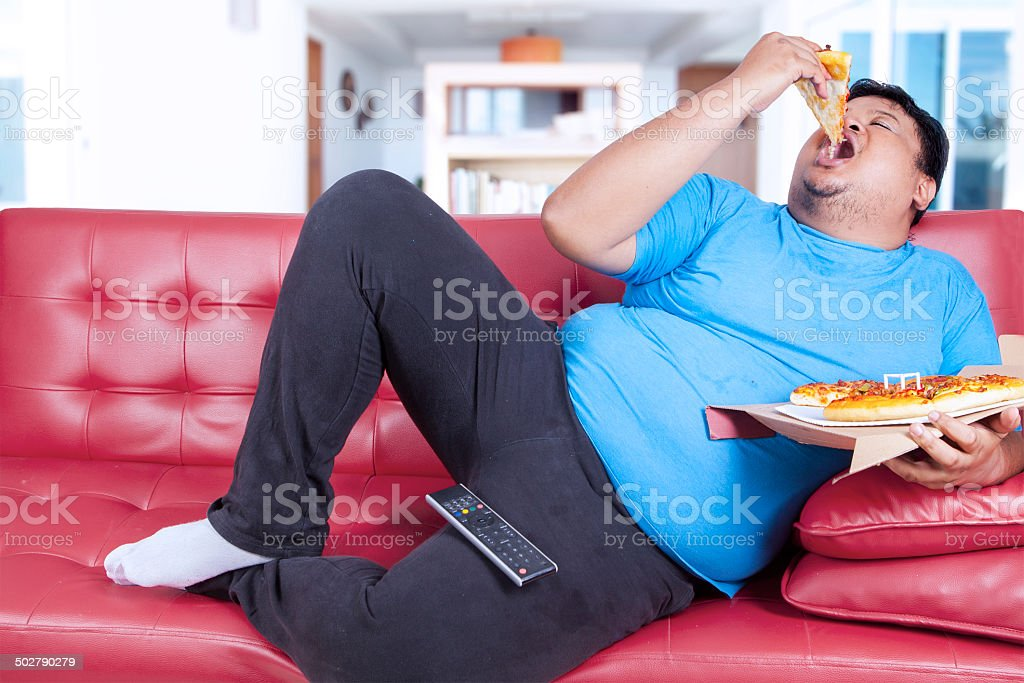 Obese person bite a slice of pizza 1 stock photo