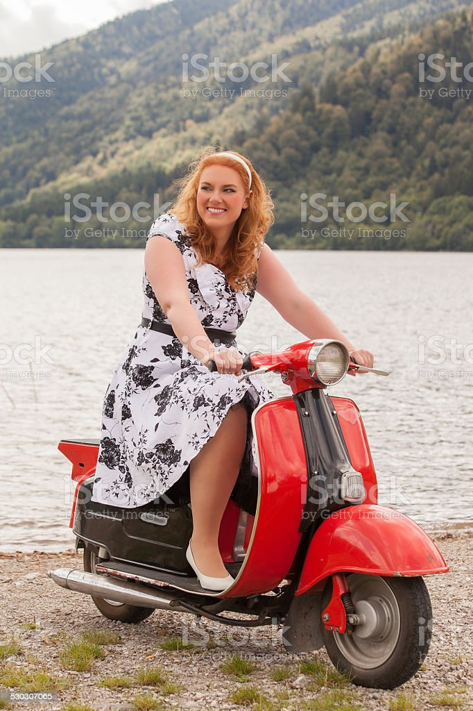 Obese redhead beauty on a red scooter stock photo