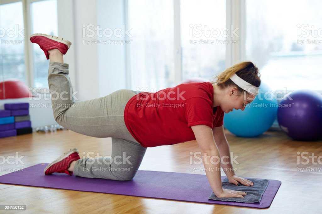 Obese Woman Doing Glute Kickback Exercise stock photo